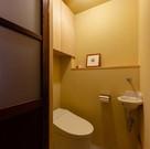 土間コンクリートと珪藻土の壁のトイレ。手洗いは建主さんチョイスのデッドスト品、ドアも同じく建主さんチョイスによるアンティーク品