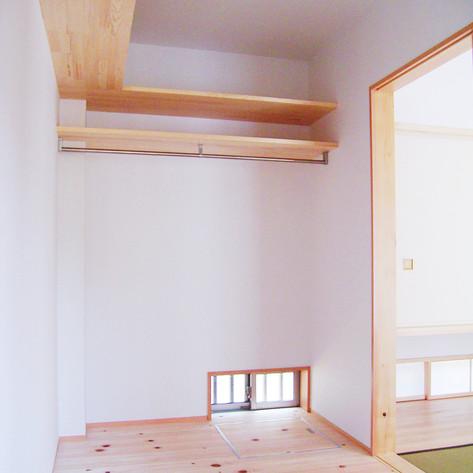 畳部屋の寝室に連続するクローゼット。通気のために足元に窓を取っている。