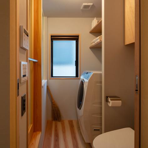 洗面脱衣と一体になったトイレ。洗濯機の搬入経路の確保をしつつ、収納スペースや便器の位置など細かく調整しています。