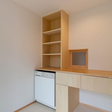 洗面脱衣・ユーティリティ室。海外製の洗濯乾燥機と一体で作られたタイル棚と作業台(下着引出)。正面の窓を開けると寝室入口。大回りすることなく収納できます。