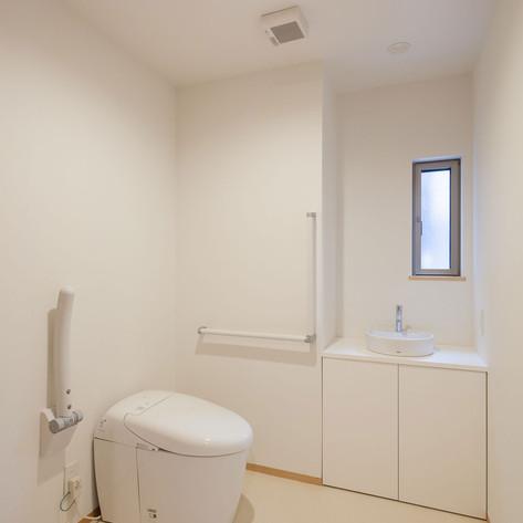 将来の高齢者の使用や車椅子での使用を想定したトイレ。さらに、便器正面の壁の向こう側は寝室となっており、その必要が発生した時に壁を壊して直接行き来できるように設計・施工されている。