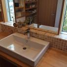 ベッセル式洗面とモザイクタイルの組合せの洗面カウンター。北側に向いた二つの縦長窓から柔らかい光が入る。