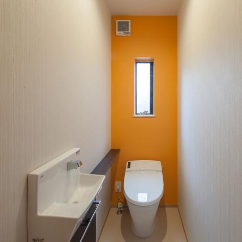 抗菌機能のある壁紙のトイレ。建主さんの希望で、風水に基づいた色で奥の壁紙をアクセントにしている。