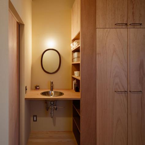 ラワン合板と珪藻土の壁の組合せ。落ち着いた洗面コーナーになります。鏡は柳宗理デザイン。