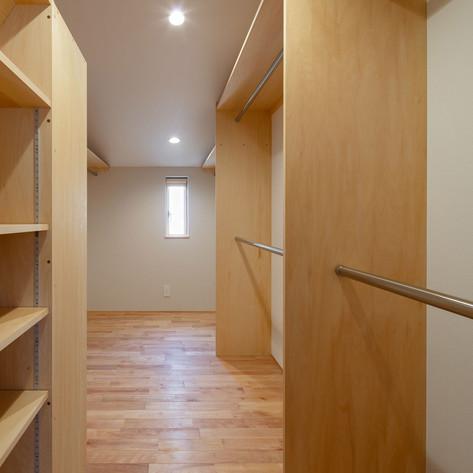 寝室に連続するウォークインクローゼット。設計にあたっての事前調査でその量を把握し、容量を決定します。右手はショート丈の衣類を上下二段でかけます。
