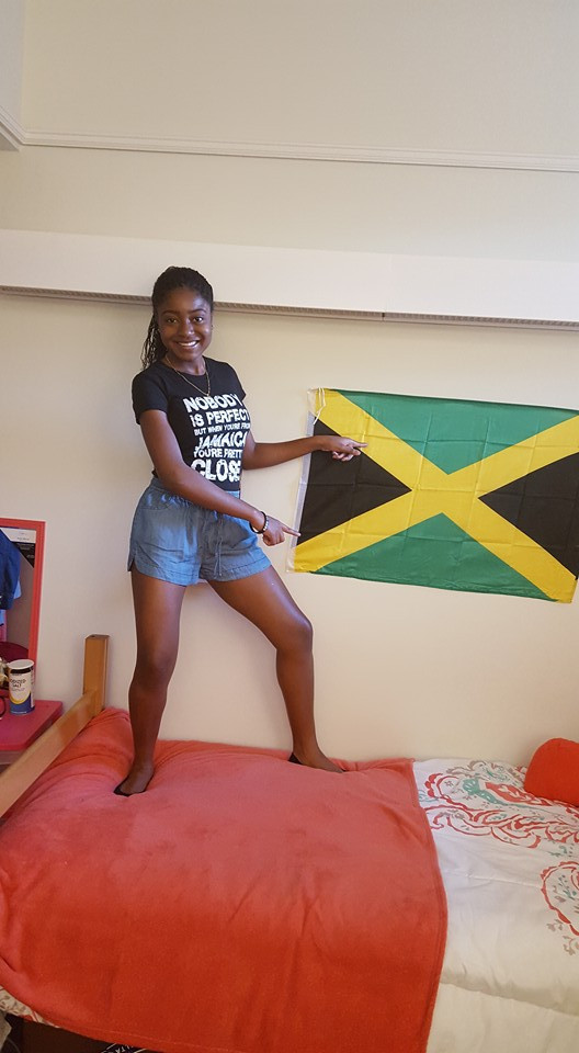 Jenine is standing on her bed in a t-shirt and shorts and is pointing to her Jamaican flag on her wall.