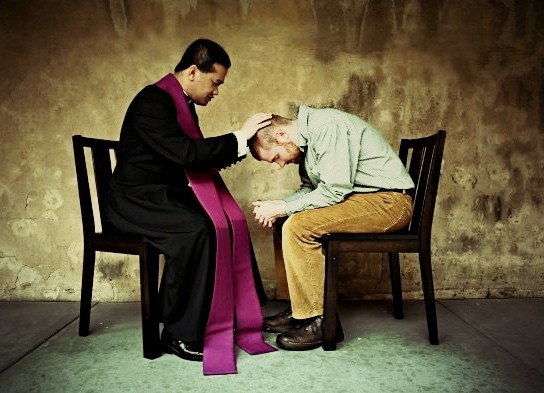 May sat in front of priest who is blessing him