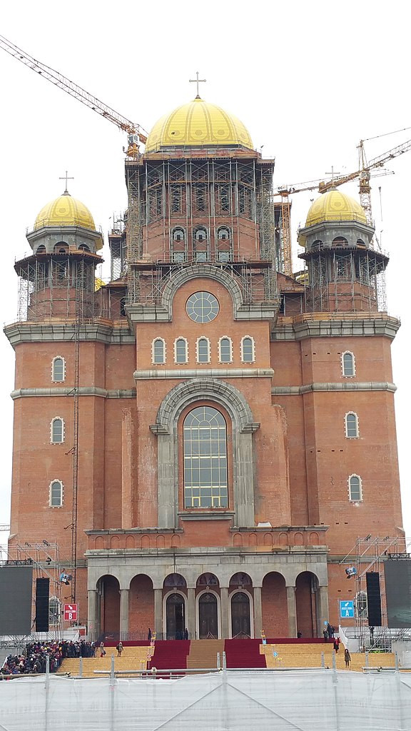 Large red brick church with golden domes under construction