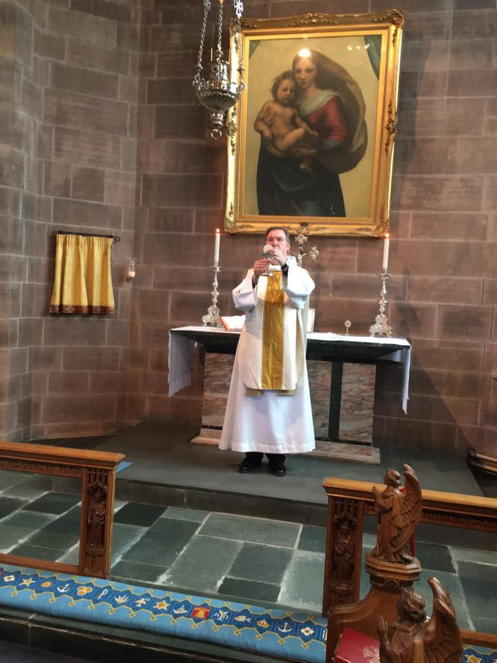 Priest stood at altar holding host and chalice.