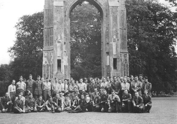 American soldiers stand under ruined arch.