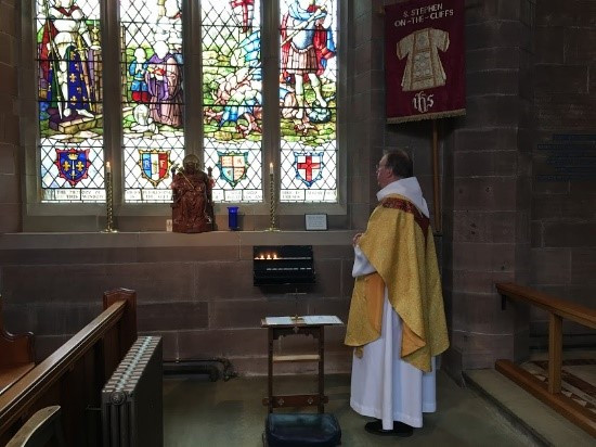 Priest in vestments stood in front of stained glass window and statue.