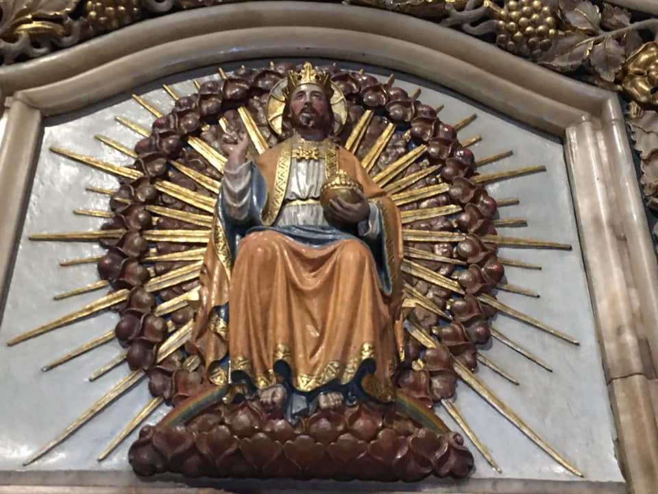Carving of Jesus crowned and sat on throne.