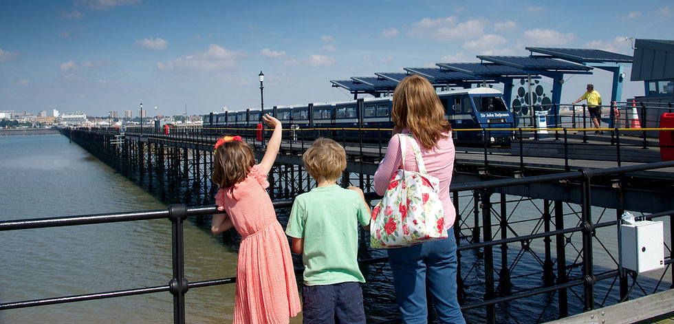 Woman and two children stand on Southend Pier, waving at the Pier Train