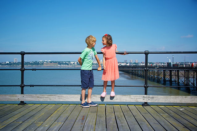 Boy and girl standing at the railings of Southend Pier, with Southend in the distance.