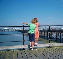 Children standing at the railings of Southend Pier pointing out to sea.