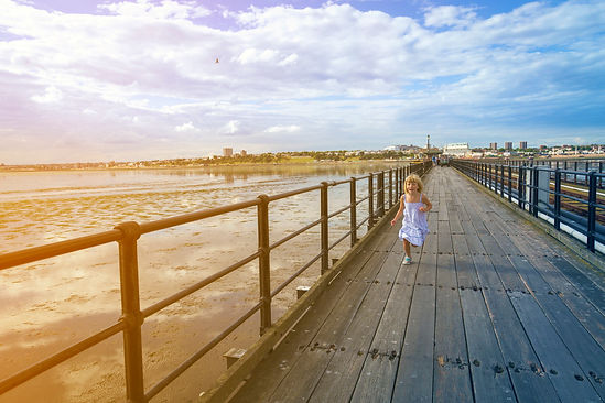 Young girl running down Southend Pier