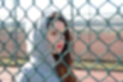 girl looking through chain fence