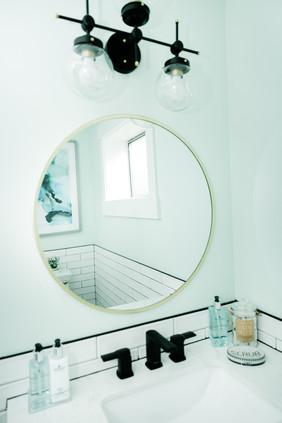mint bathroom white tile details Amanda George Interior Design round modern mirro