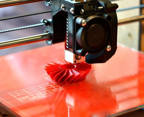 3D printer prints red form.jpg