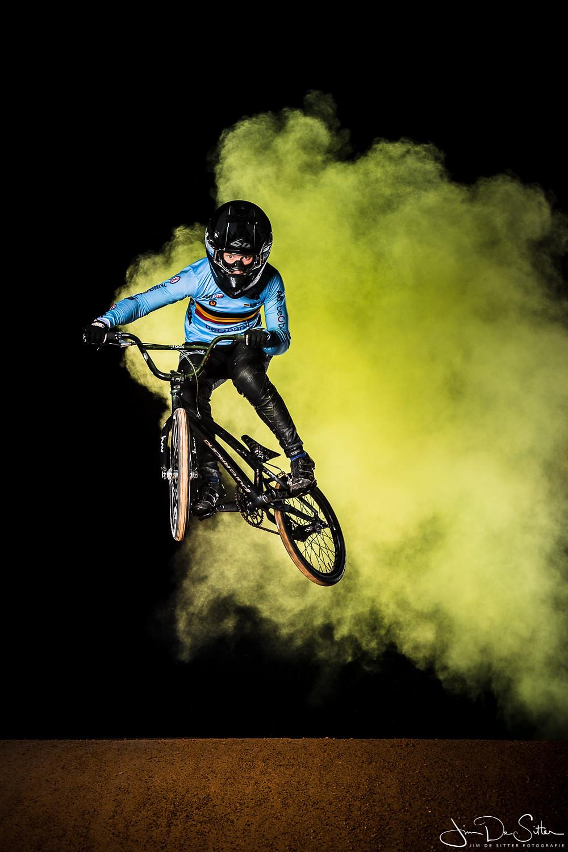 Kampioene Elke Vanhoof springt met haar BMX door een poederwolk