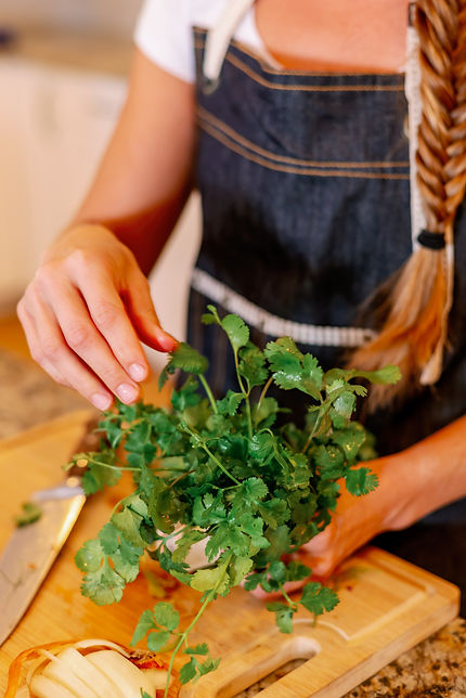 Chef Lisa holding a bunch of cilantro in kitchen