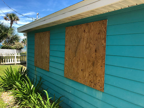 Homemade plywood shutters cover a beach
