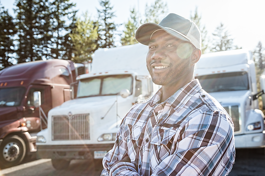 BLACKMANSTANDINGINFRONTOFSEMITRUCKS.png