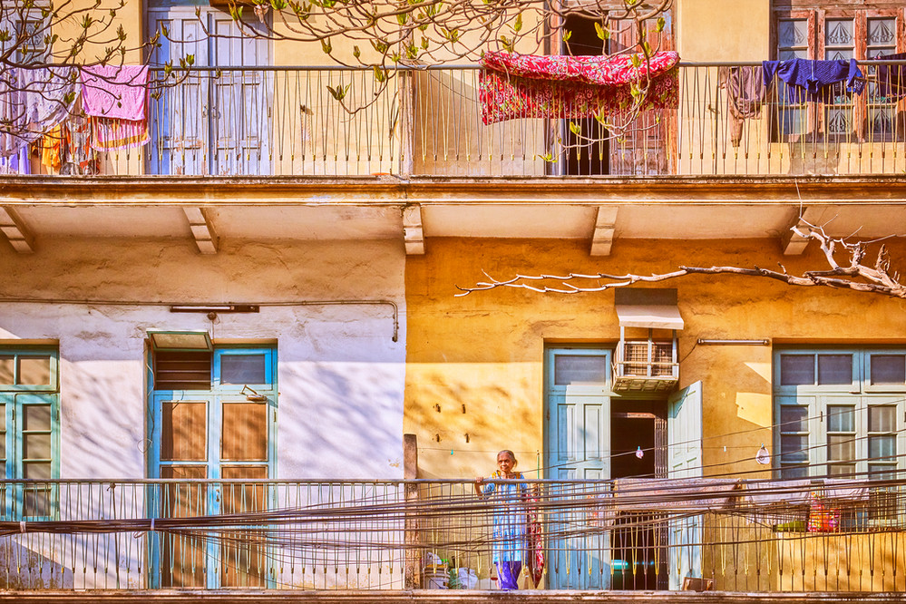 Old lady on colorful balcony