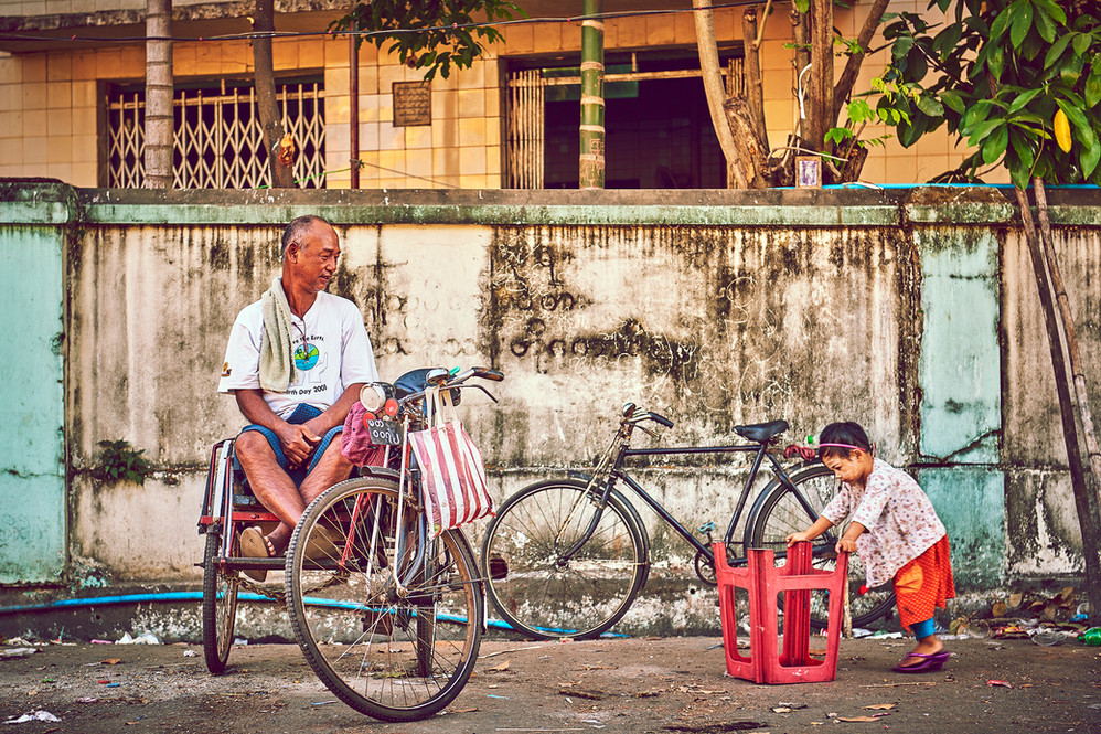 Guy waiting is his rikshaw while little girl is playing