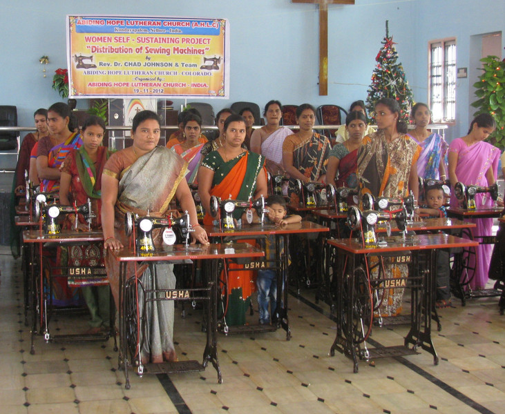 A groups of women are presented with sewing pachines as they complete their training as seamstresses.