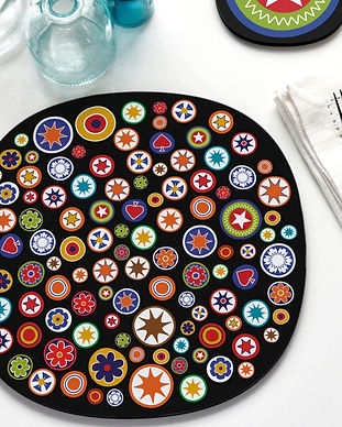 A placemat with a colourful millefiori design on a black background in a tablescape