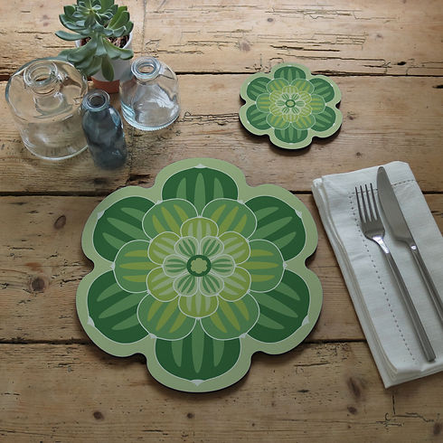 A green designer placemat and coaster with a contemporary flower shaped design in a rustic table setting