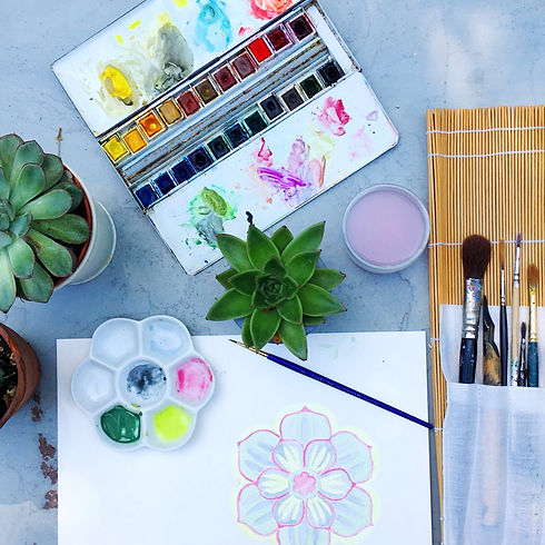 A flatlay showing watercolours, brushes and colour palette for a placemat design in progress