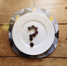 A rustic table setting with a modern geometric design placemat and a question mark on a plate made out of blueberries