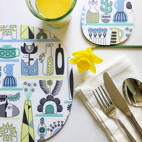A fresh quirky shelf life placemat and coaster design in blue and yellow on a spring table setting