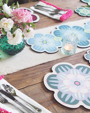 A rustic alfresco tablescape featuring a centrepiece table mat in a succulent design with matching placemats and coasters