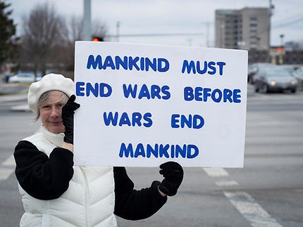 "Nancy holding a sign saying ""Mankind must end wars before wars end mankind."""