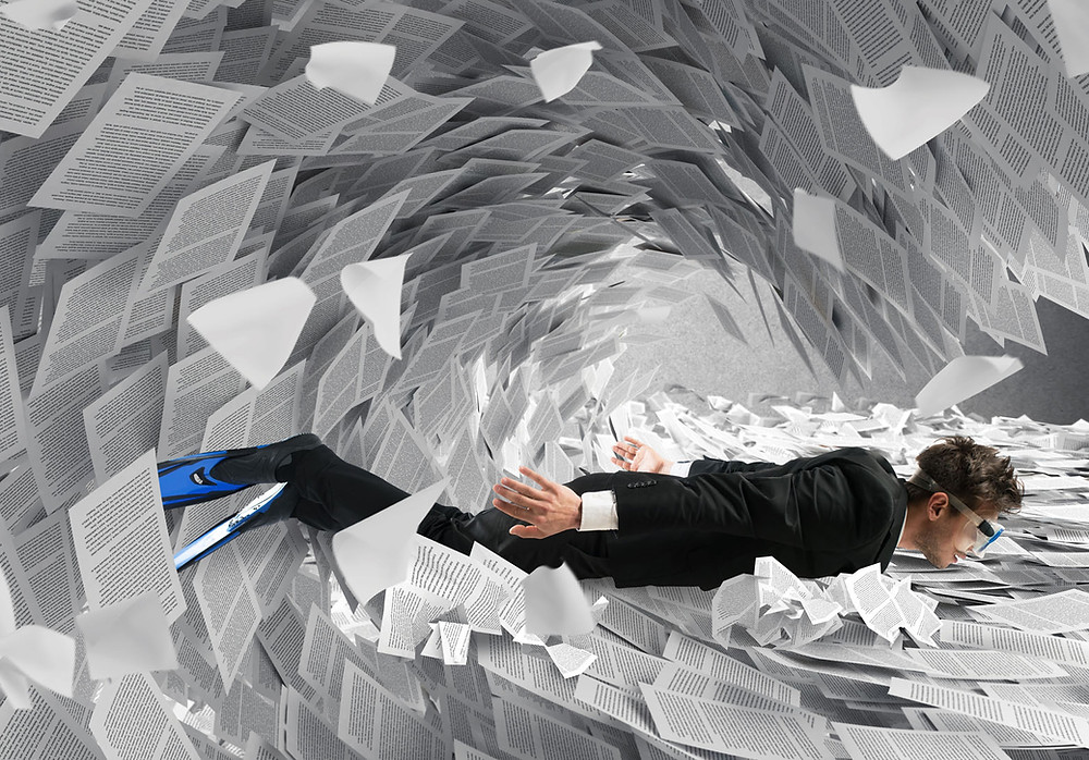 Man in suit, swim fins and goggles swimming a crashing wave of paper: metaphor for dealing successfully with work others drown in