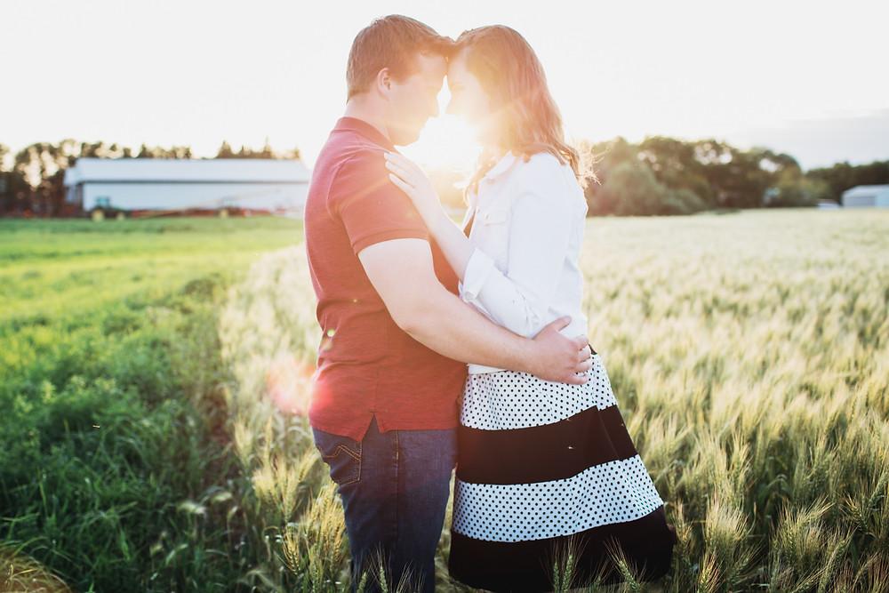 The sun shines through couple as they pose on their farm.