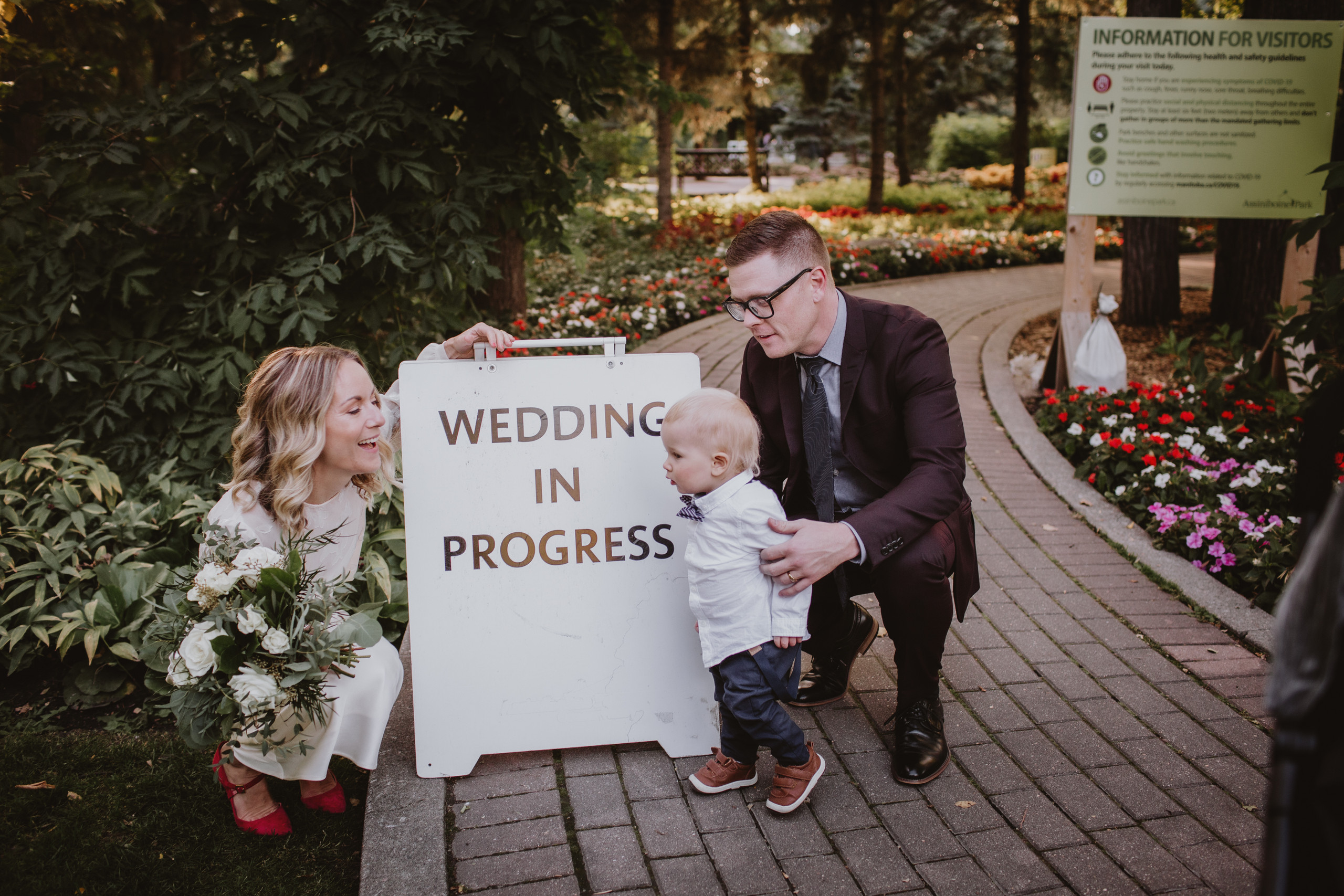 Wedding In Progress - Bride, groom and son pose by sign at their Assiniboine Park micro wedding.