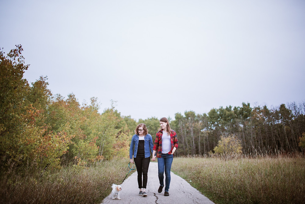 Couple walks their dog in along the forest path during photo session.