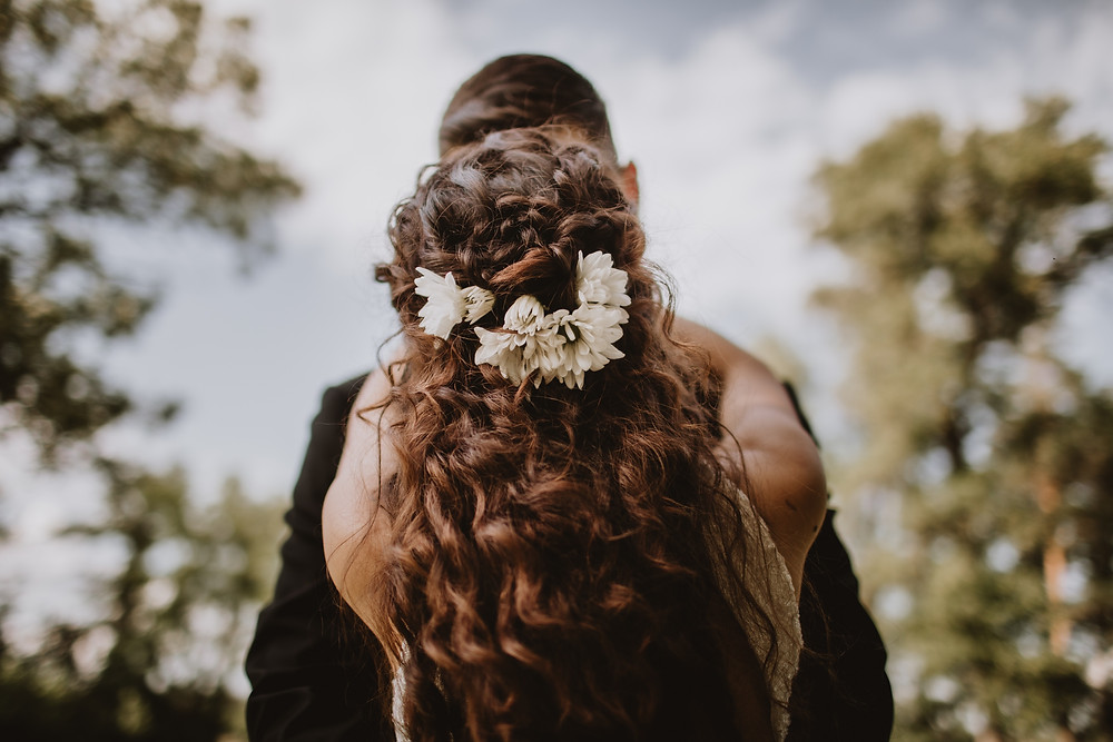 Curly, long bridal hair with white daisies.