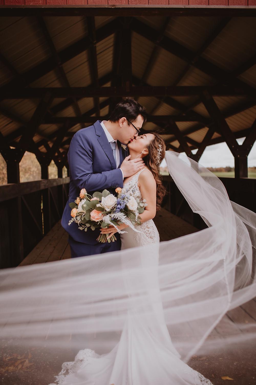 Bride and groom kiss during wedding portraits on bridge.