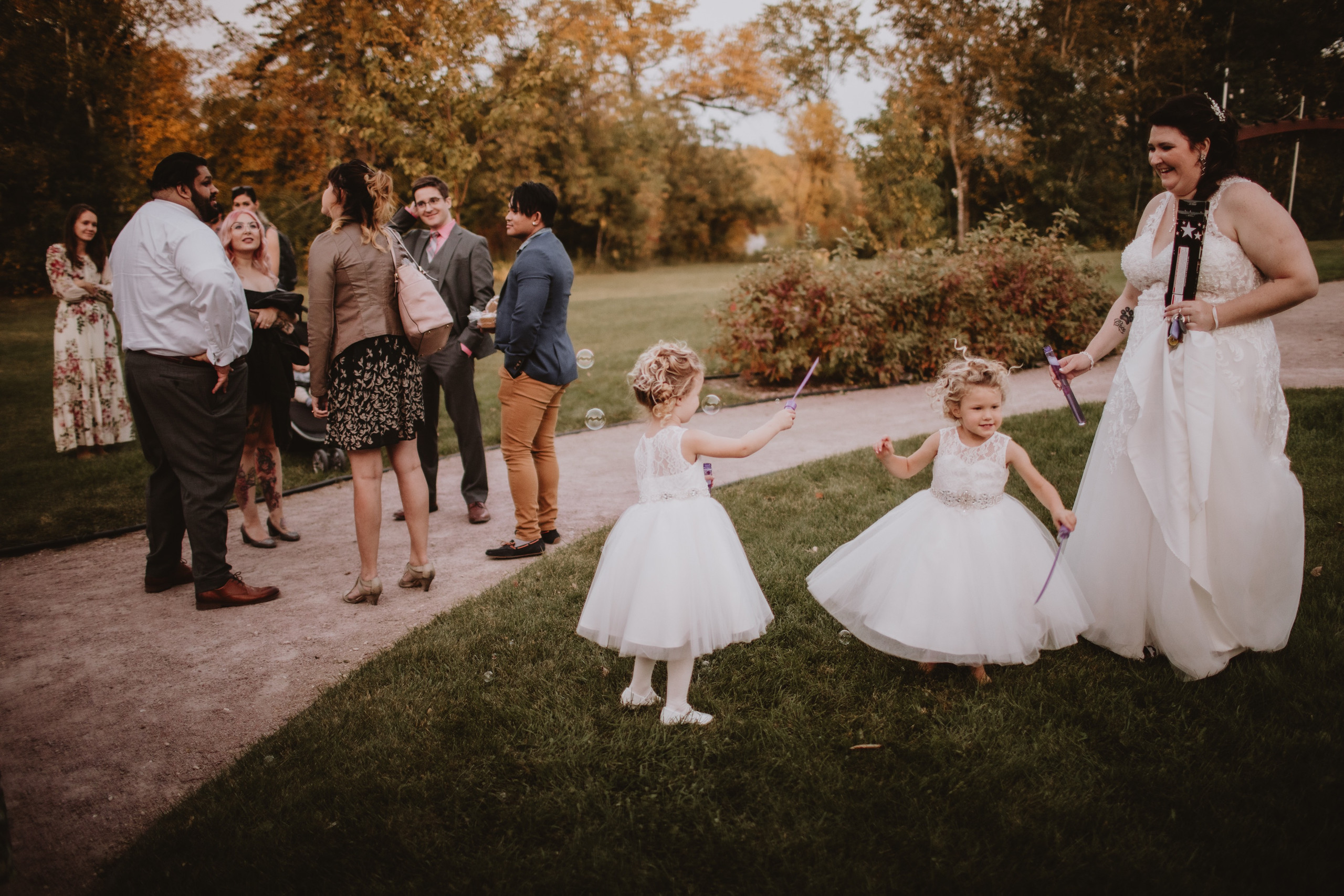 Flower Girls play with bubbles during wedding reception.