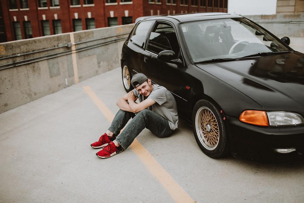 Manitoba graduate poses with his car.
