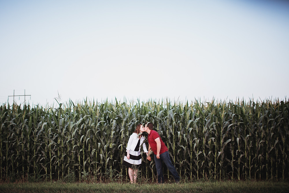 couple kisses in cornfield during engagement photos.