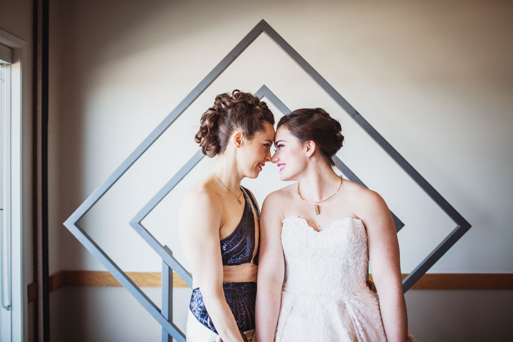 Bride touch noses and foreheads for portrait in front of arche.