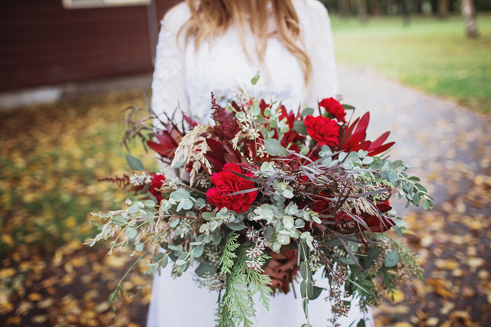 Red bridal bouquet with hearty greens. Wedding in Clear Lake, Manitoba.