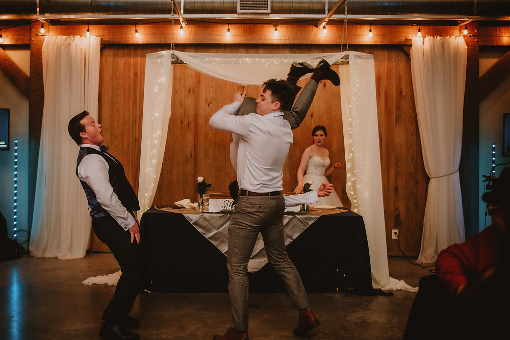 Groomsen do a flip during special number at wedding reception.