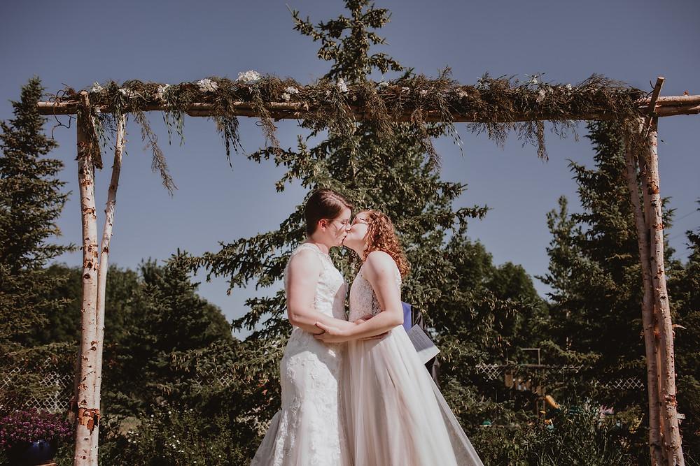 Brides kiss under birch arch.